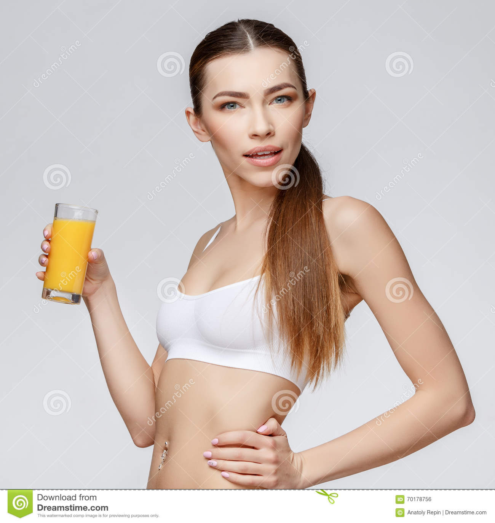 Sportig kvinna över hållande exponeringsglas för grå bakgrund av orange fruktsaft