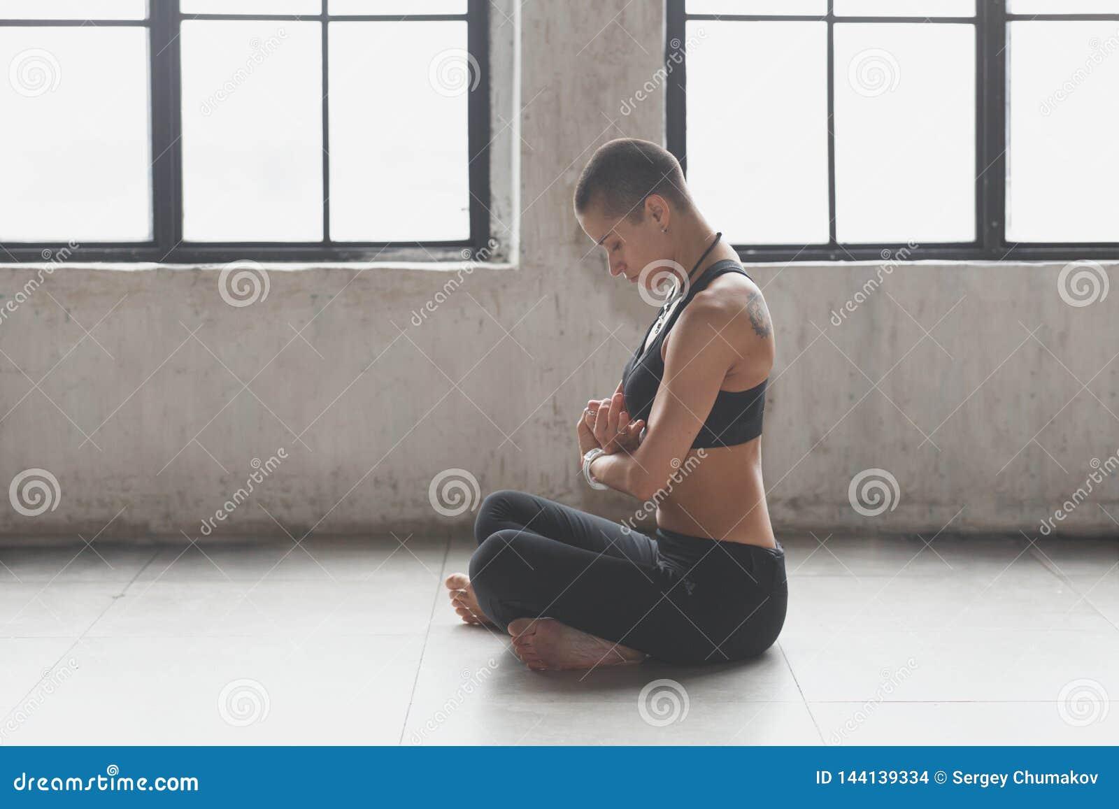 Sportig kvinnlig g?rande yoga n?ra f?nster