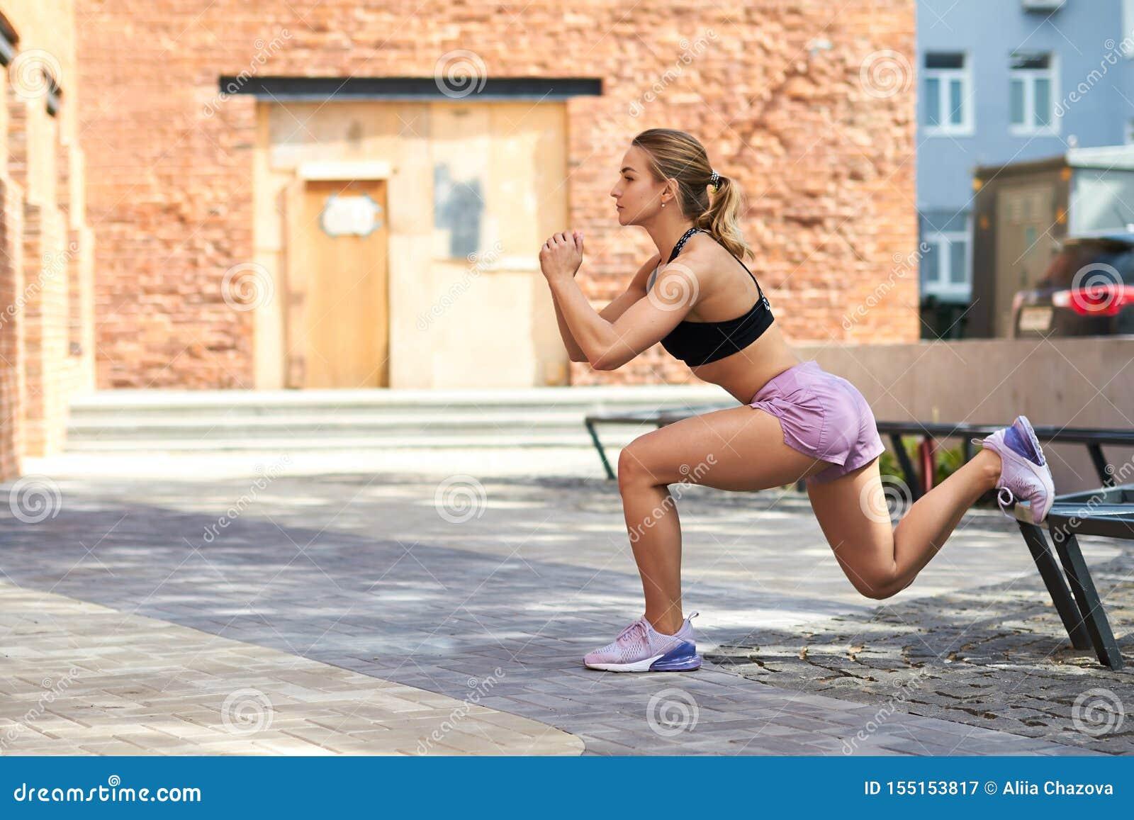 Sportig slank flicka i svart överkant och kortslutningar som gör utfallövning