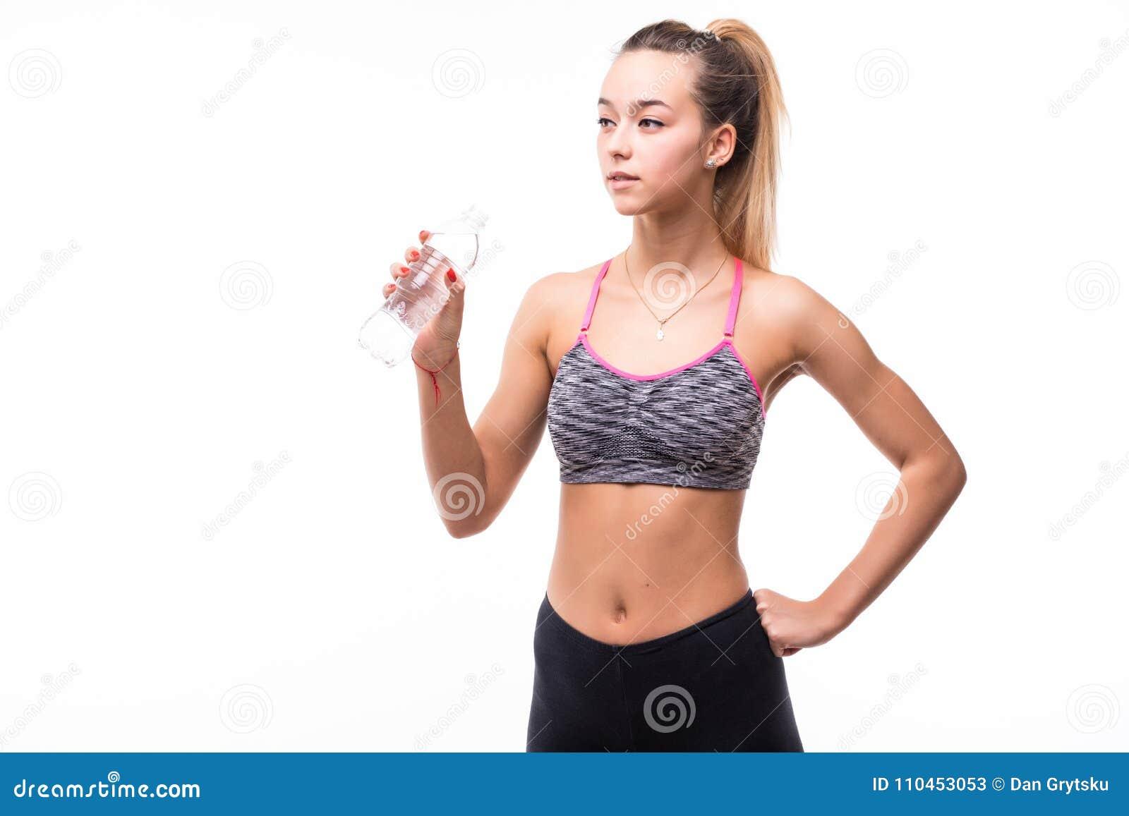 Sportigt muskulöst kvinnadricksvatten mot vit bakgrund