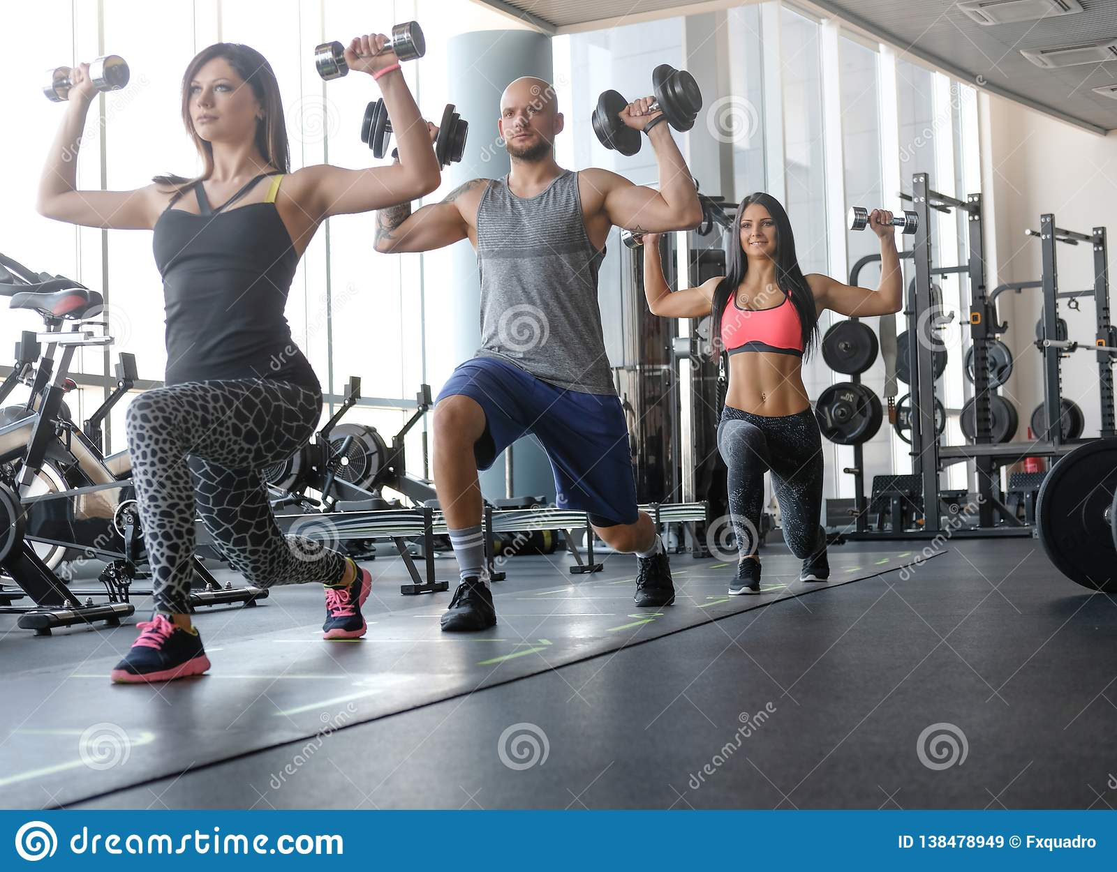 Two beautiful girls with their coach doing functional crossfit training with dumbbells in the gym.