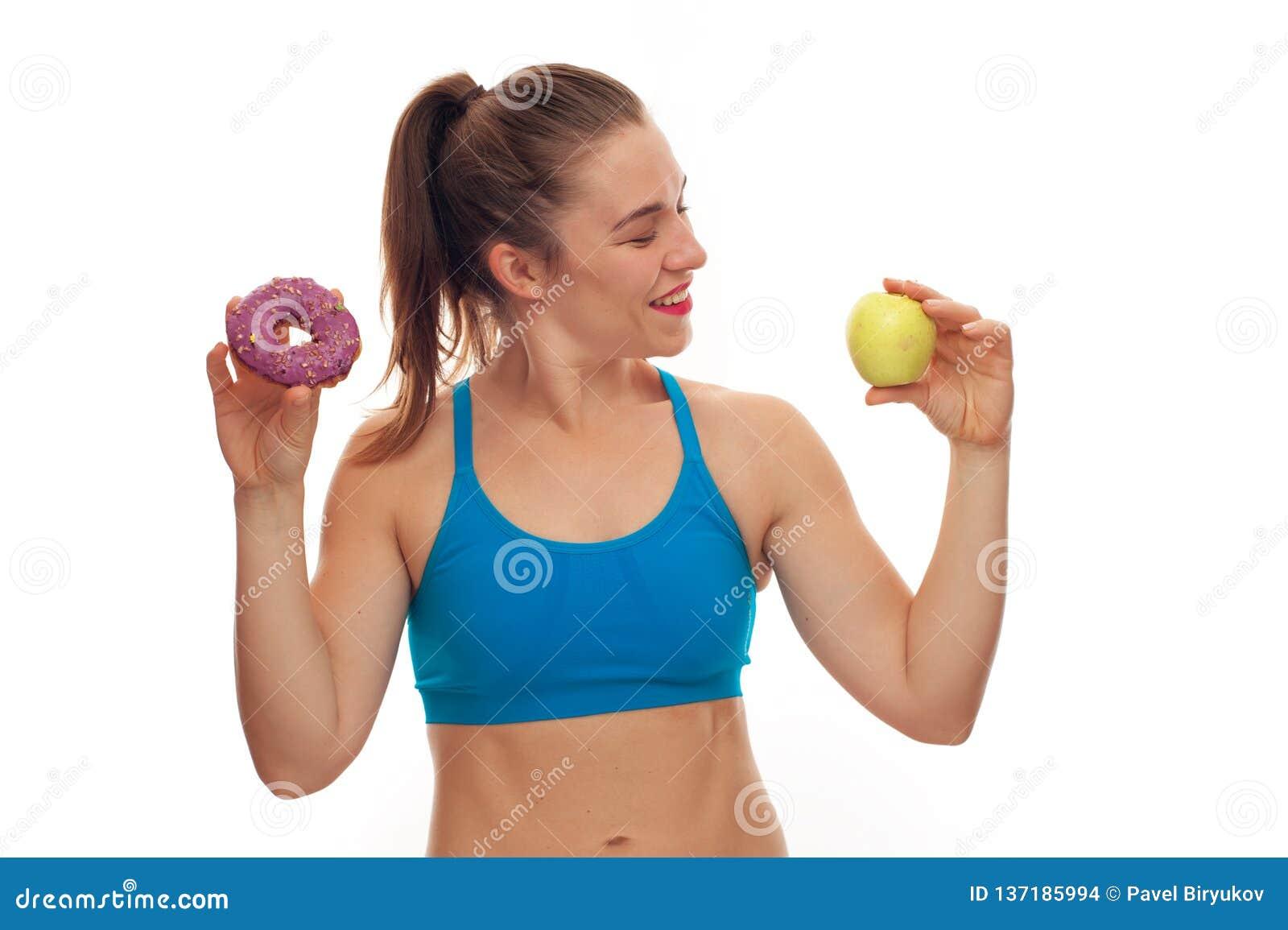 Sportive kvinna som väljer mellan munken och äpplet