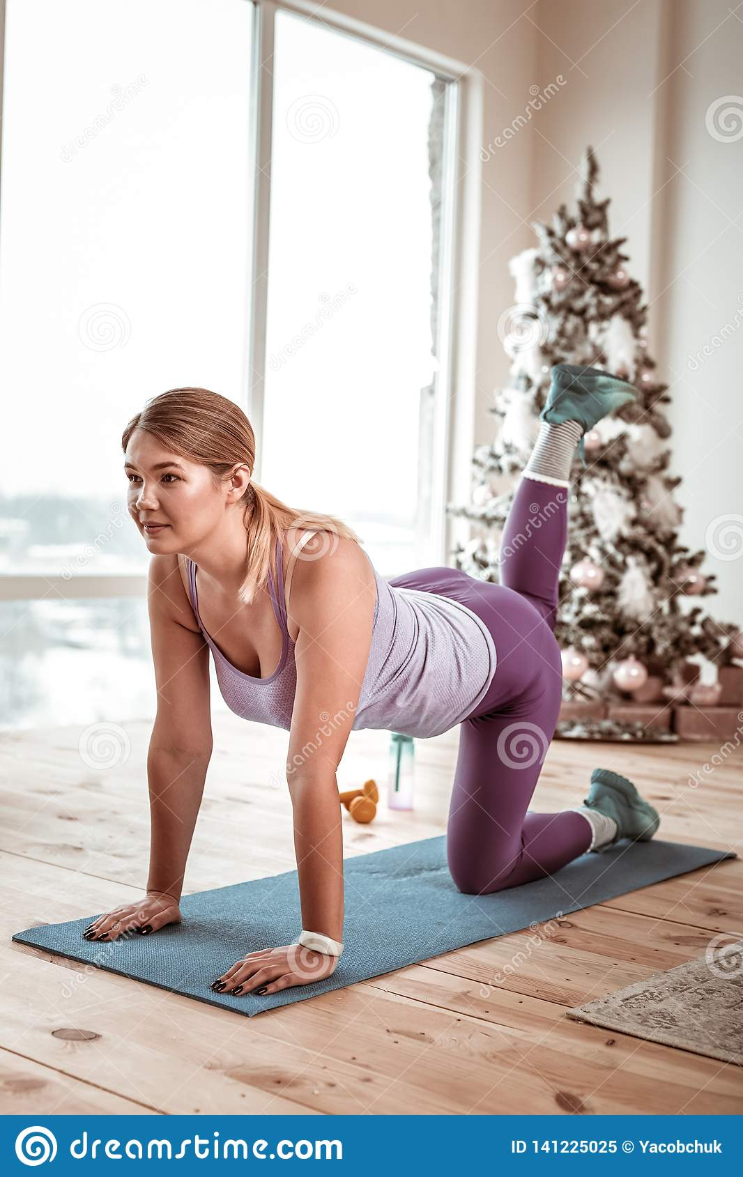 Sportive lady in violet shiny leggings doing plank on rubber mat