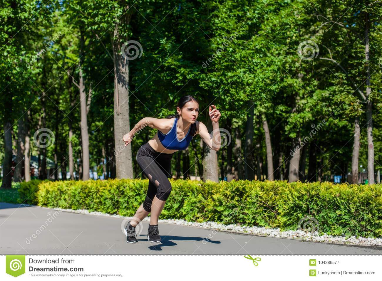 8906d2a0fc114 Young sportive teen in a bright blue sport bra and black leggings running  in the park. Photo of an athlete girl with a beautiful sports body