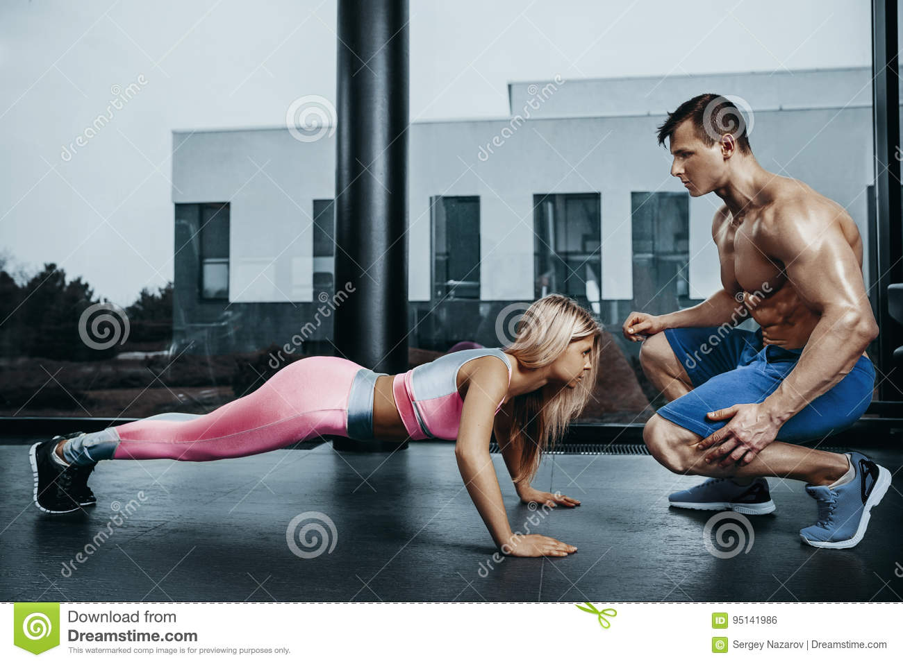 Sportive woman doing plank exercise training back and press muscles with trainer. Sport fitness workout strength power