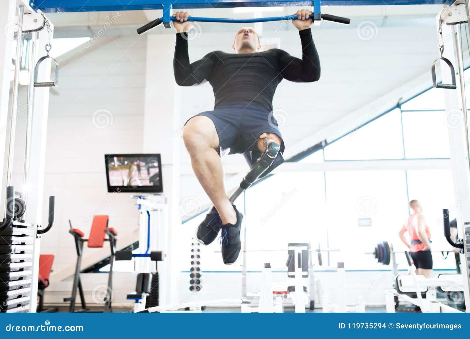 Sportivo adattabile muscolare che utilizza le macchine di esercizio nella palestra
