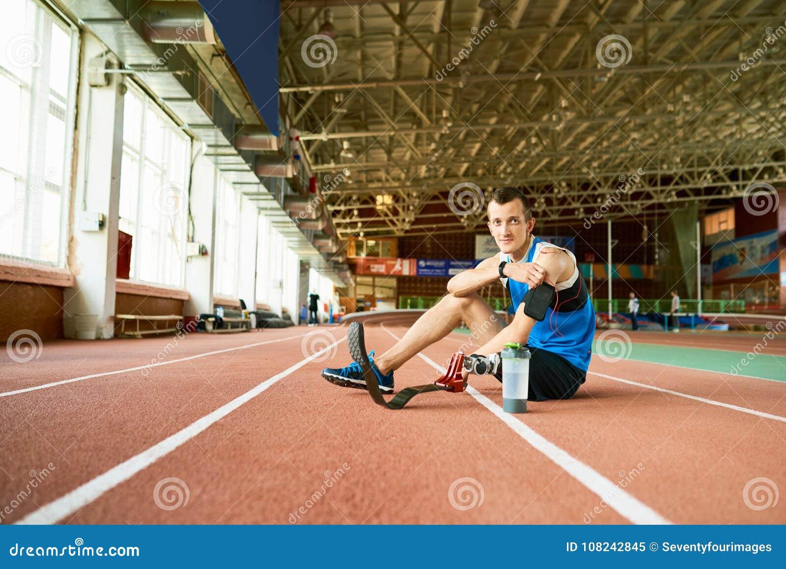 Sportivo handicappato che si siede sulla pista corrente