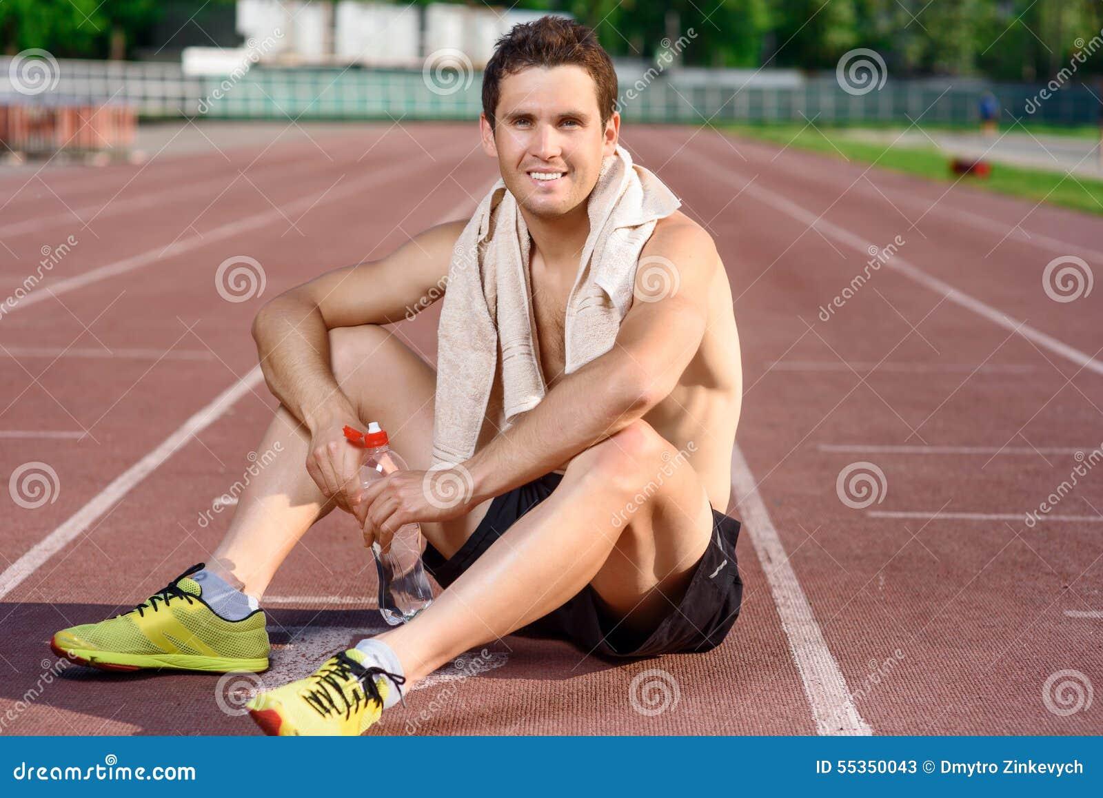 Sportivo sorridente che si siede e che ha resto