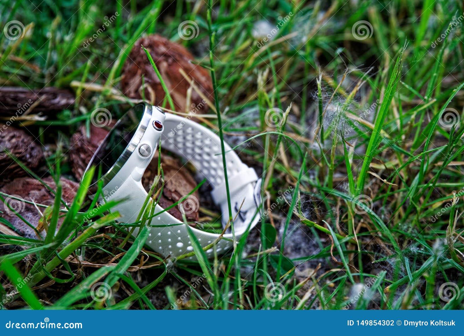 Sportklocka för körande vit färg på jordningen i gräset Konditionklocka för spårande daglig aktivitets- och styrkautbildning