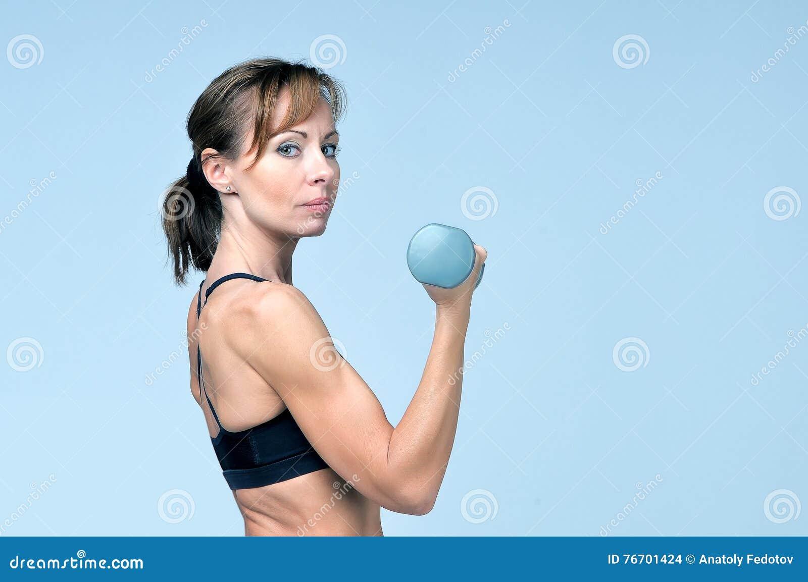 Sportkonditionkvinna som gör övning med hantlar