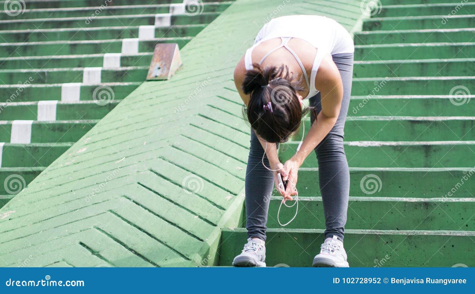 Sportkvinna som använder mobiltelefonspring i stads- byggnad för stad