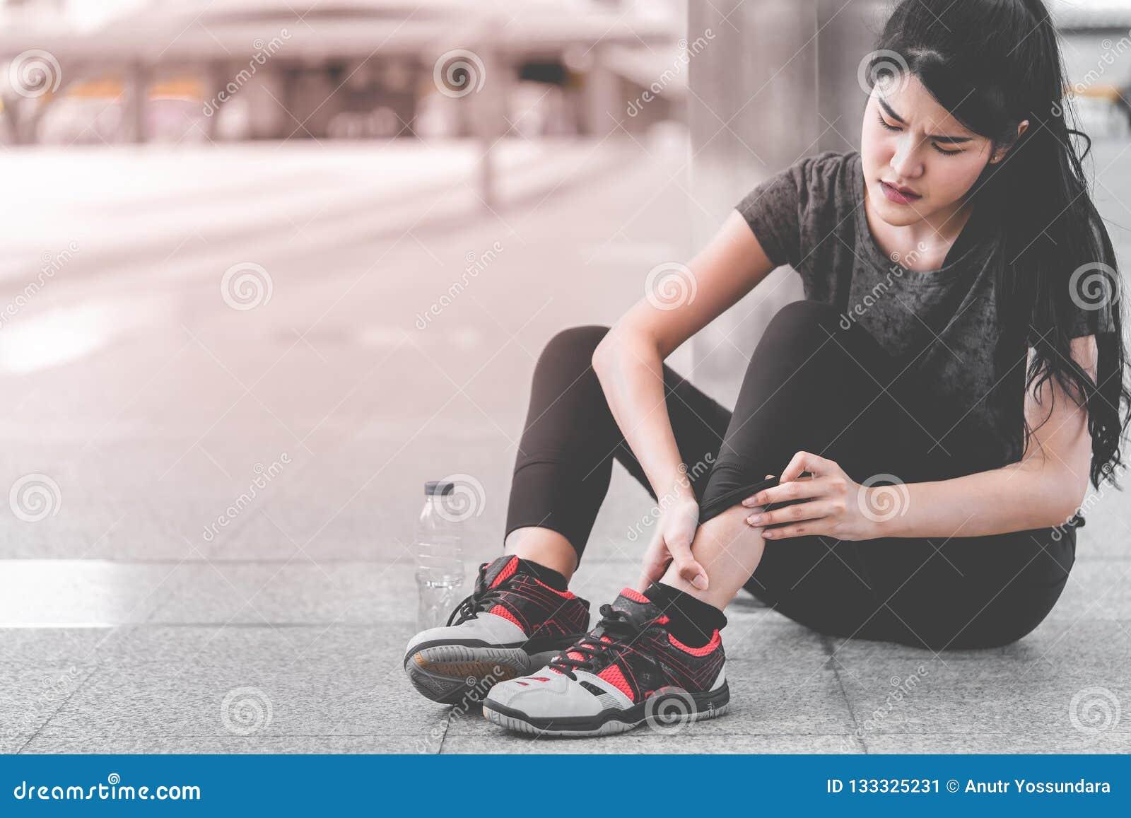 Sportkvinna som har en skada på hennes ankelfot