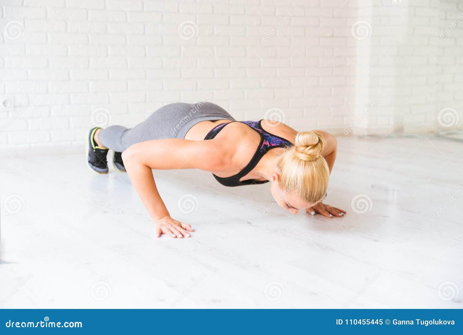 Sportkvinna som poserar i photostudio över tegelstenväggen Konditionmotivation