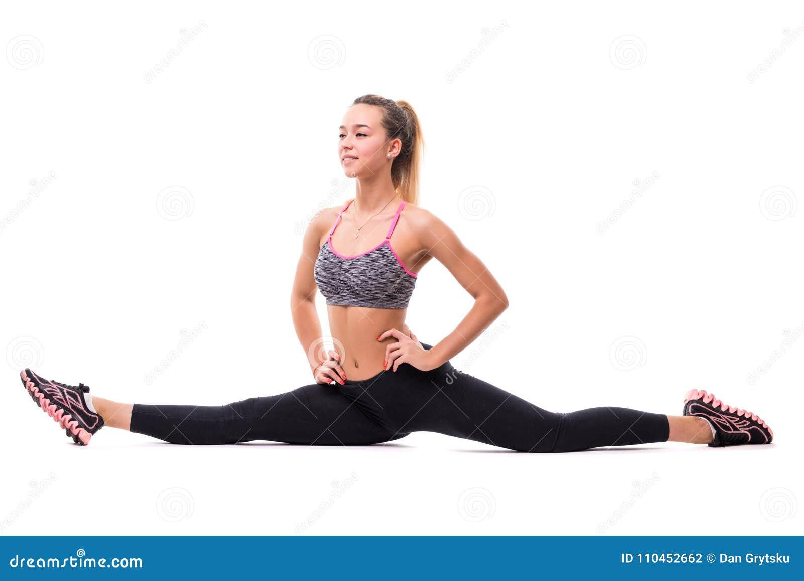 Sportkvinnan i sportwear sitter på en tvinna som isoleras på en vit bakgrund