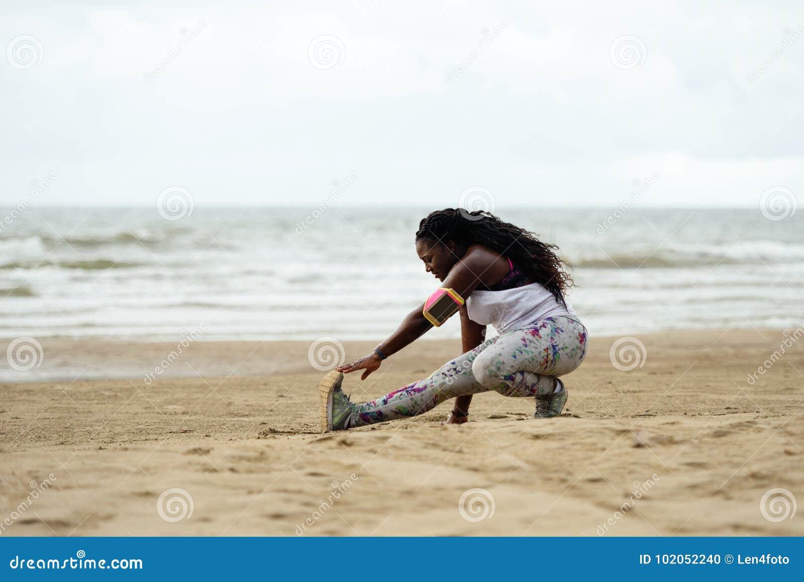 Sportliche attraktive afrikanische Frau, die Übungen auf dem Strand tut