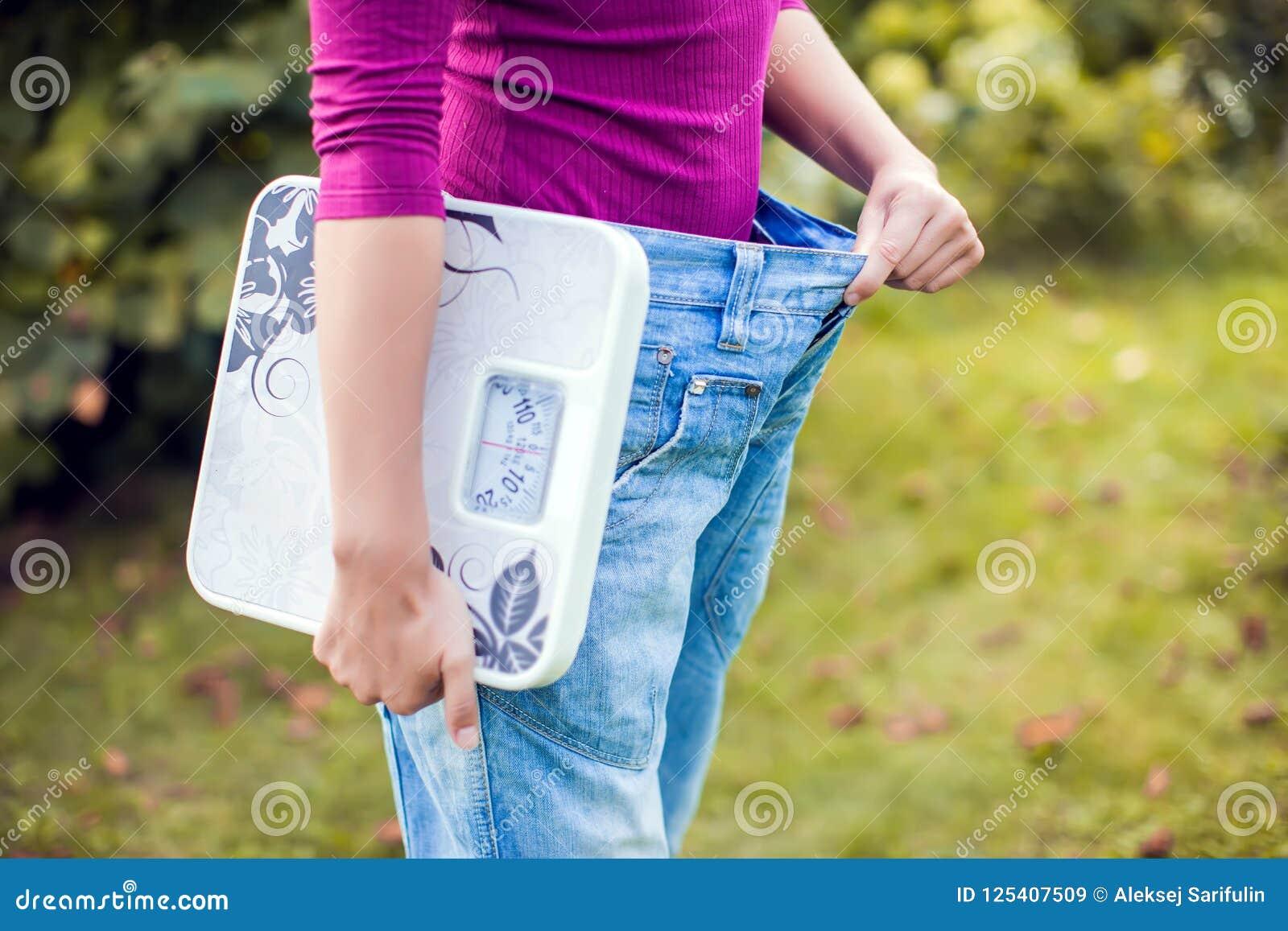 Sportliche Frau, die große Hosen zeigt und Skalen hält Gewichtsverlust c