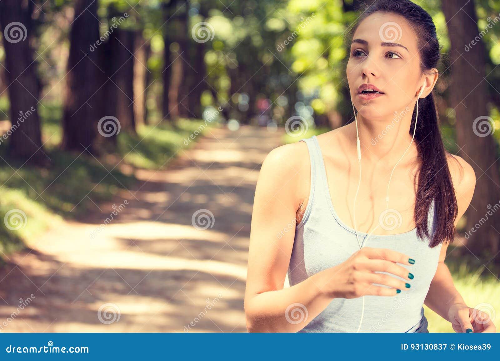 Sportliche Frau, die im Park im Sonnenaufganglicht rüttelt