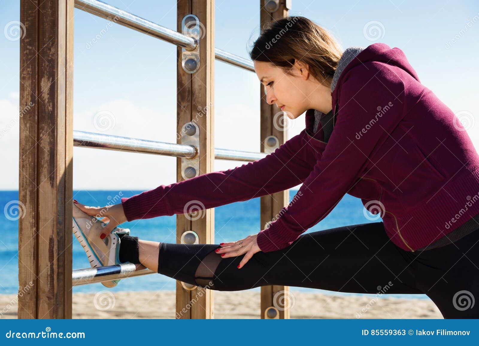 Sportliche Frau, die am Seestrand trainiert