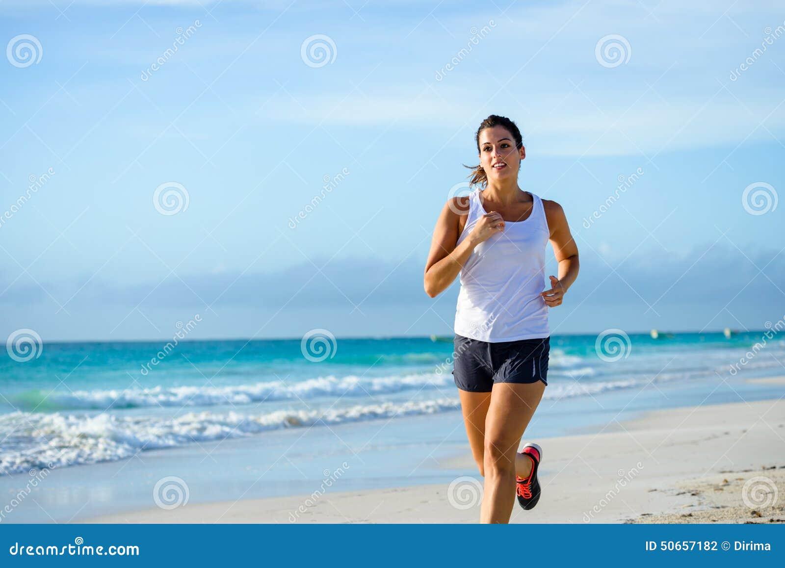 Sportliche Frau, die am tropischen Strand läuft