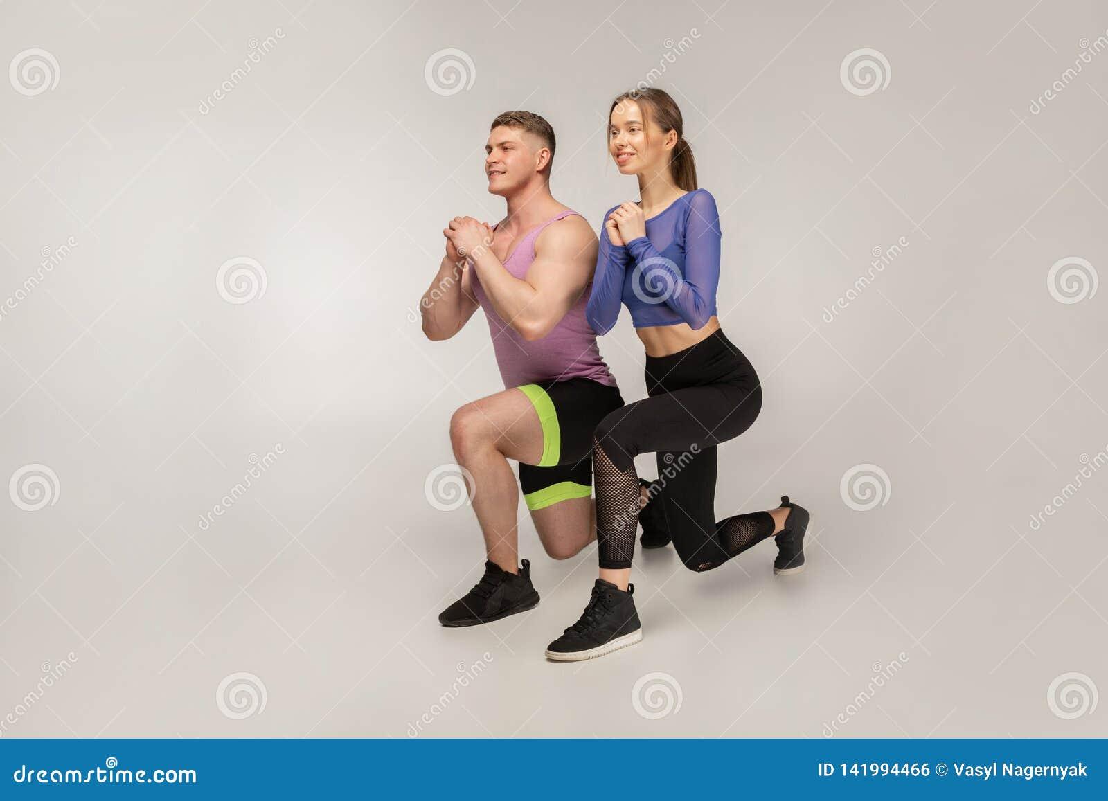 Sportliche junge Paare in der modischen bunten Sportkleidung, die Laufleine auf linkem Fuß tut