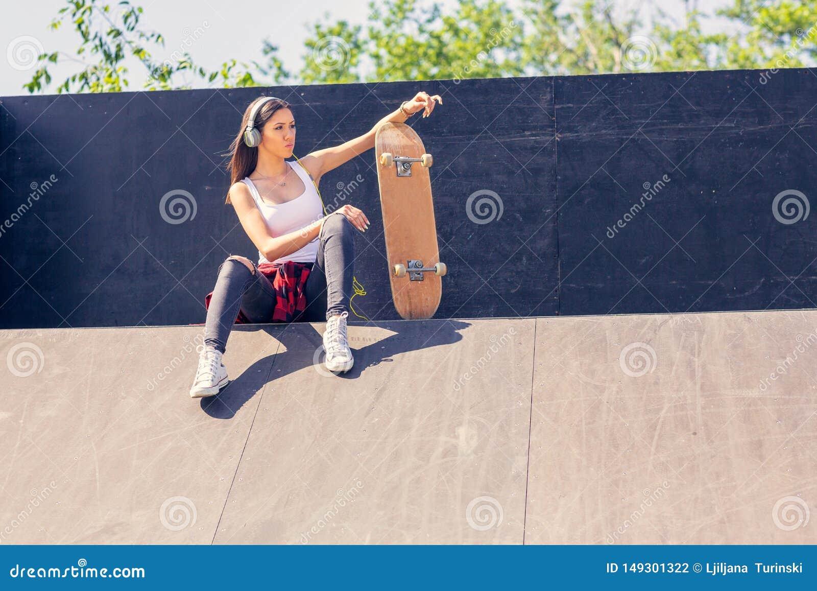 Sportliches jugendlich M?dchen mit h?render Musik des Skateboards Drau?en st?dtischer Lebensstil