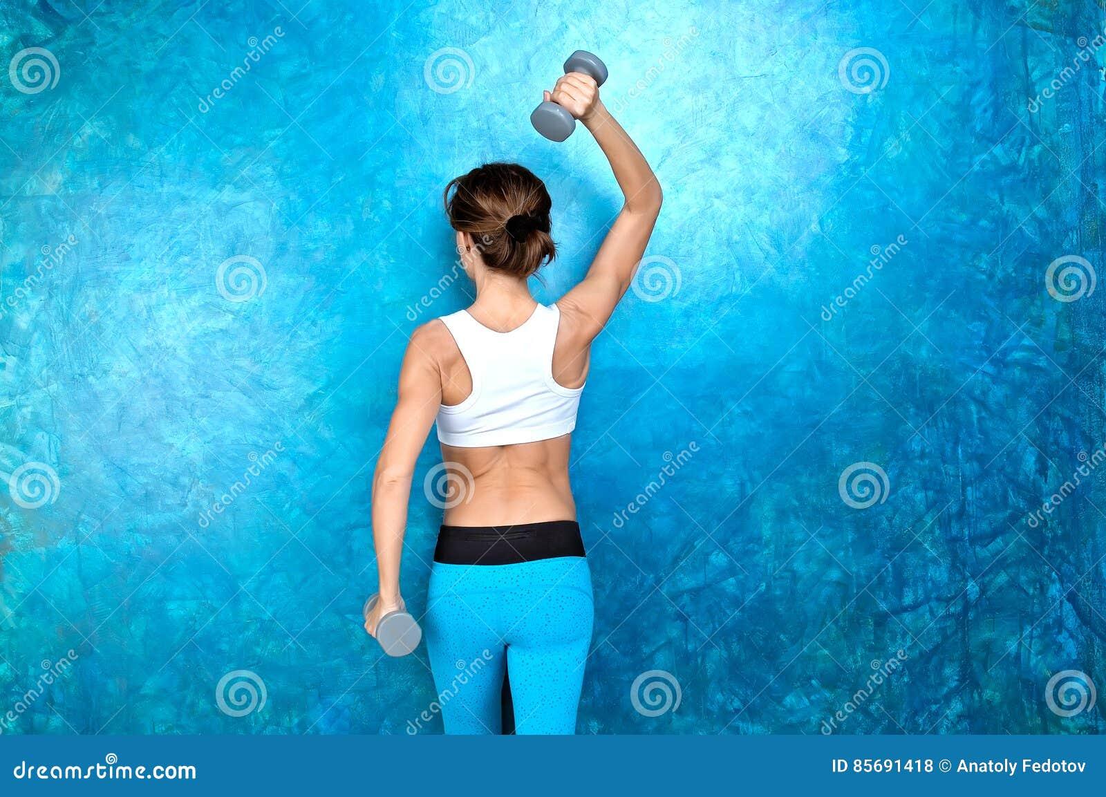 Sportmädchen, das Trainingsübung mit Dummköpfen tut Schießen in St.