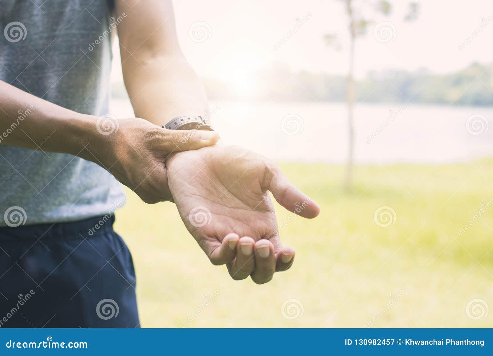 Sportman som lider handen och armen som sårar som övning och workou