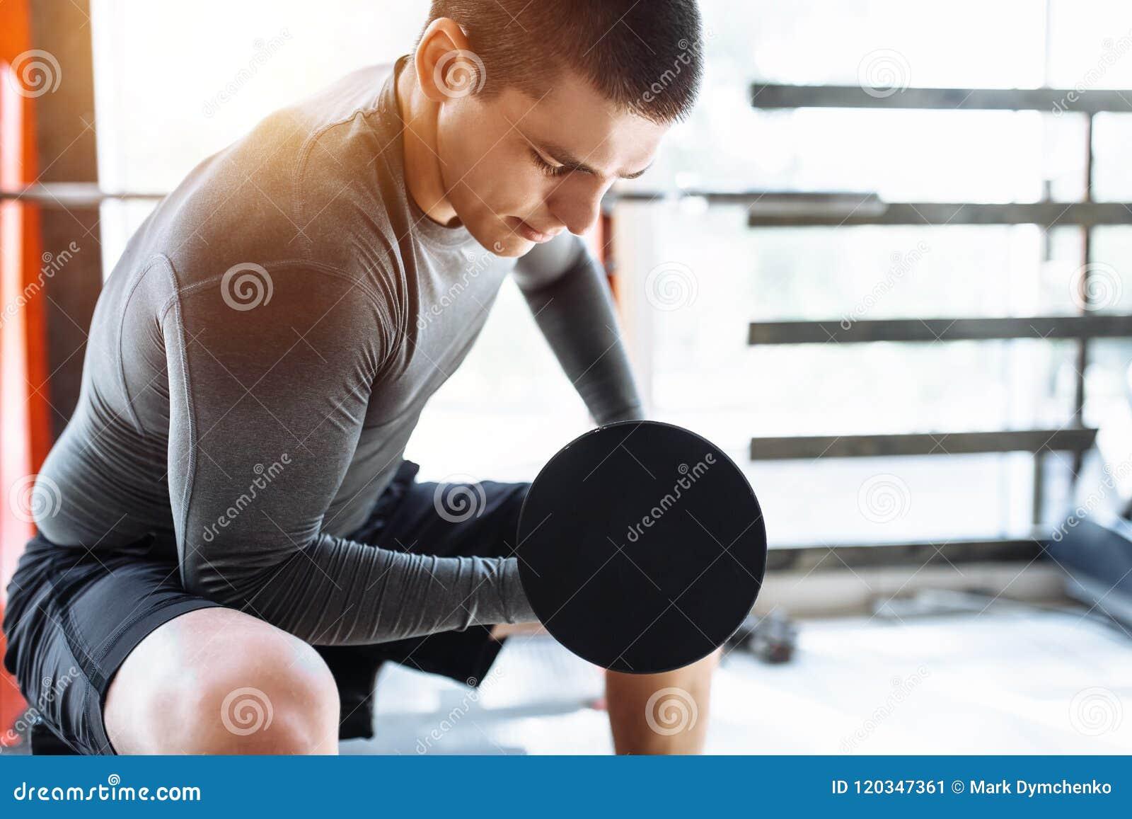 Sportmannen lyfter vikter i utbildning i idrottshallen, morgonutbildning