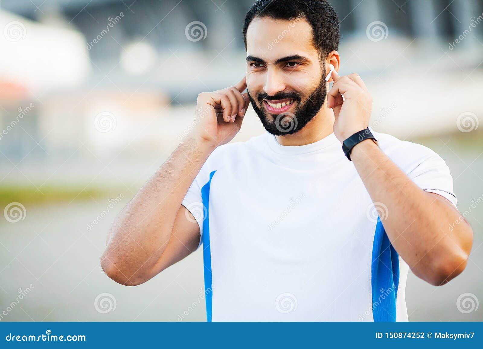Sportmens die die hoofdtelefoons voor het luisteren muziek op ochtend met behulp van in park in werking wordt gesteld
