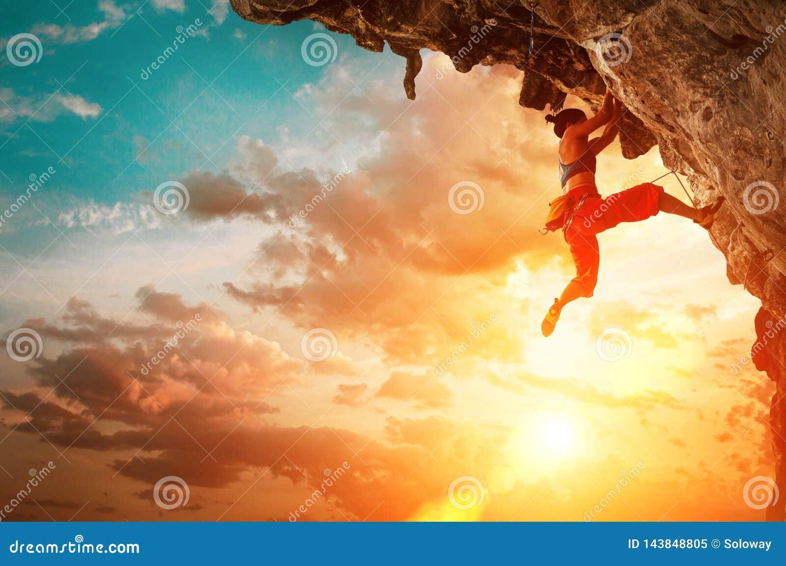 Sportowy kobiety pięcie na nawisłej falezy skale z zmierzchu nieba tłem
