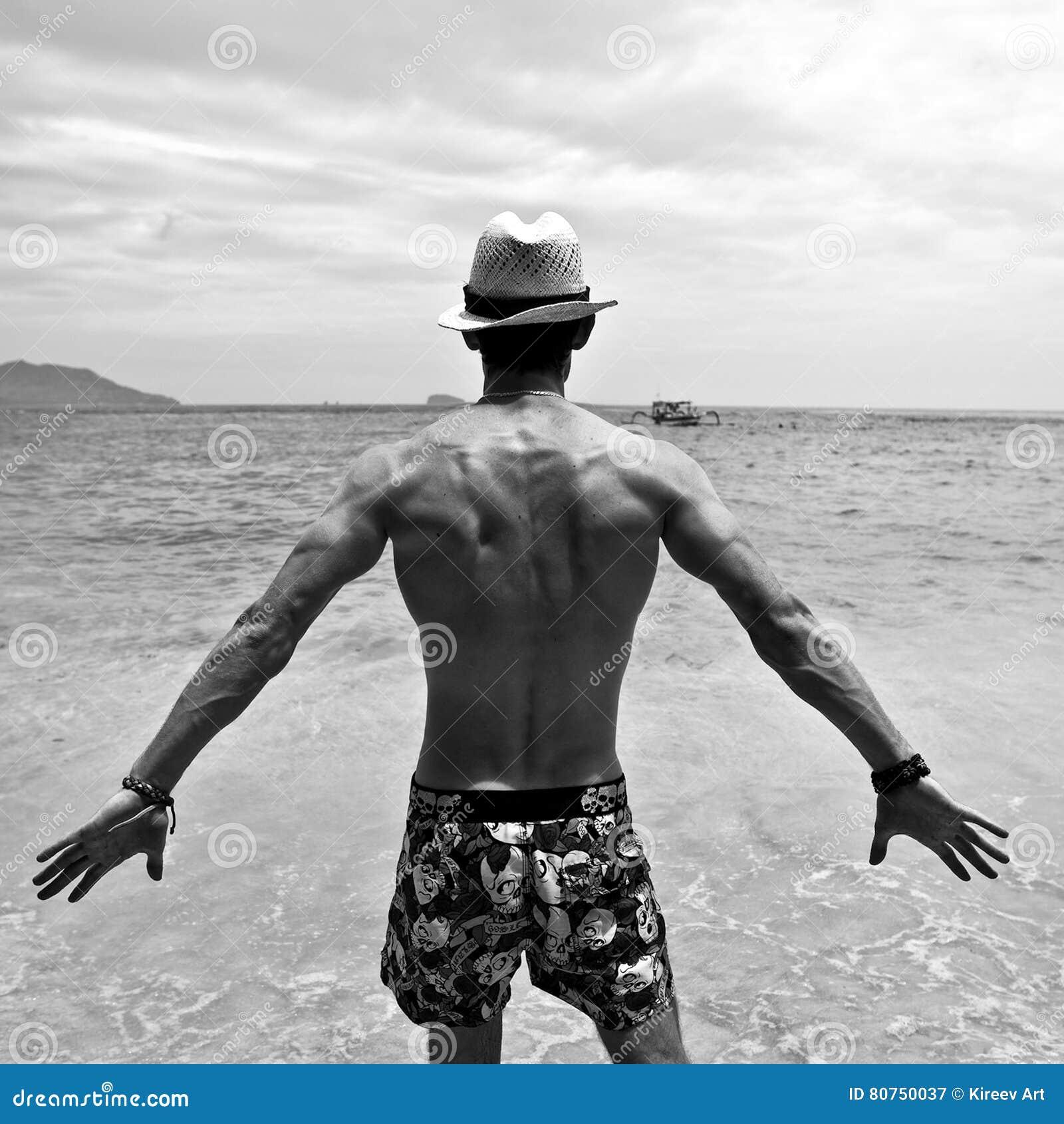 Sportowy mężczyzna pobyt z powrotem na plaży Biała fotografia