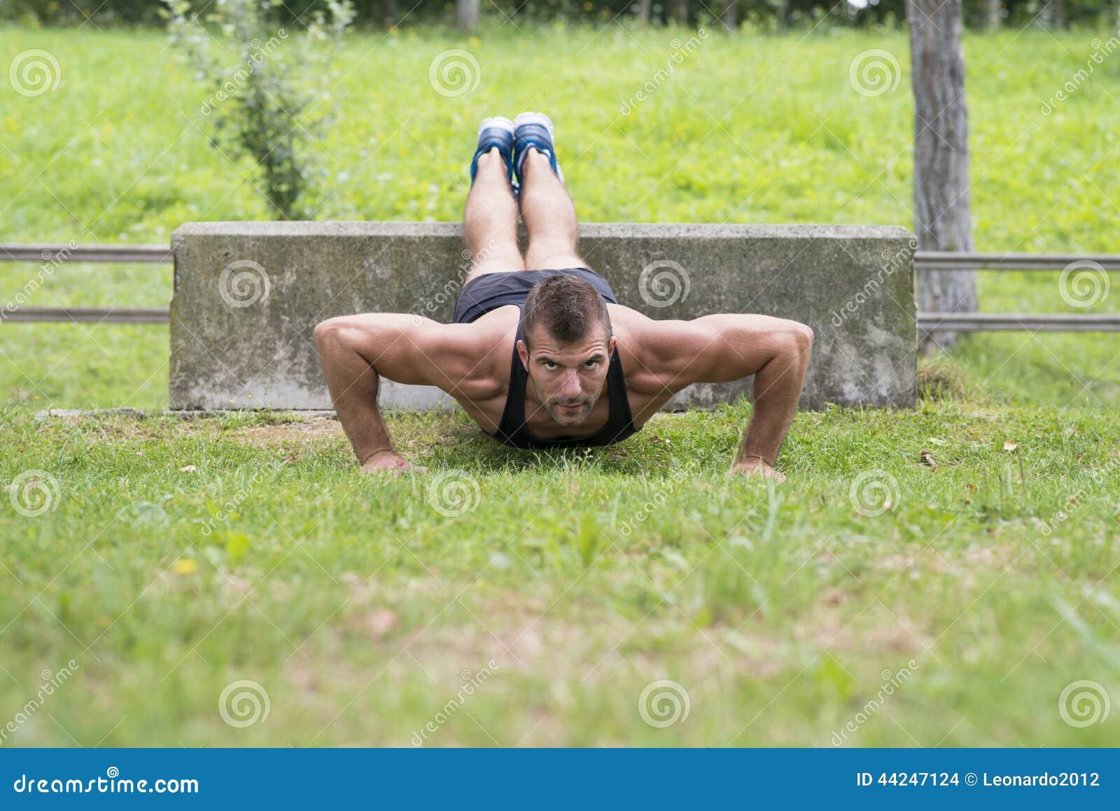 Sportowy mężczyzna podnosi, plenerowy robić pcha