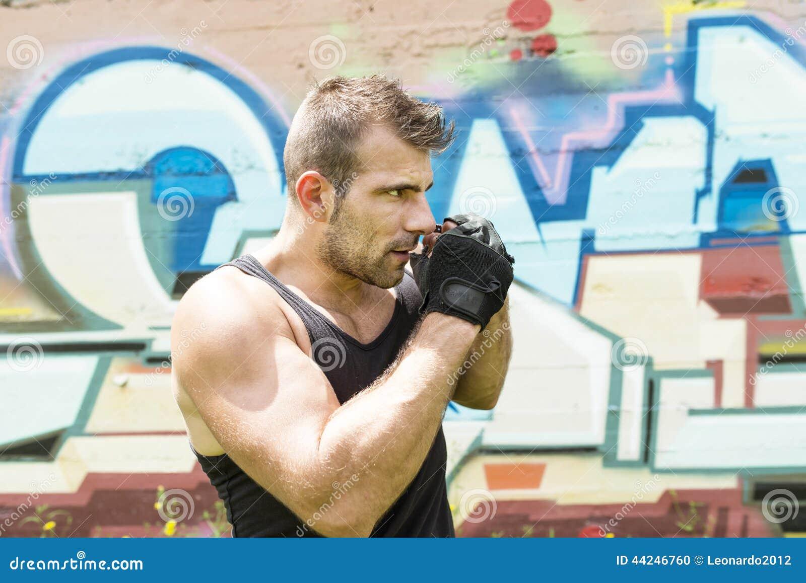 Sportowy mężczyzna wojownik w boks pozie, miastowy styl