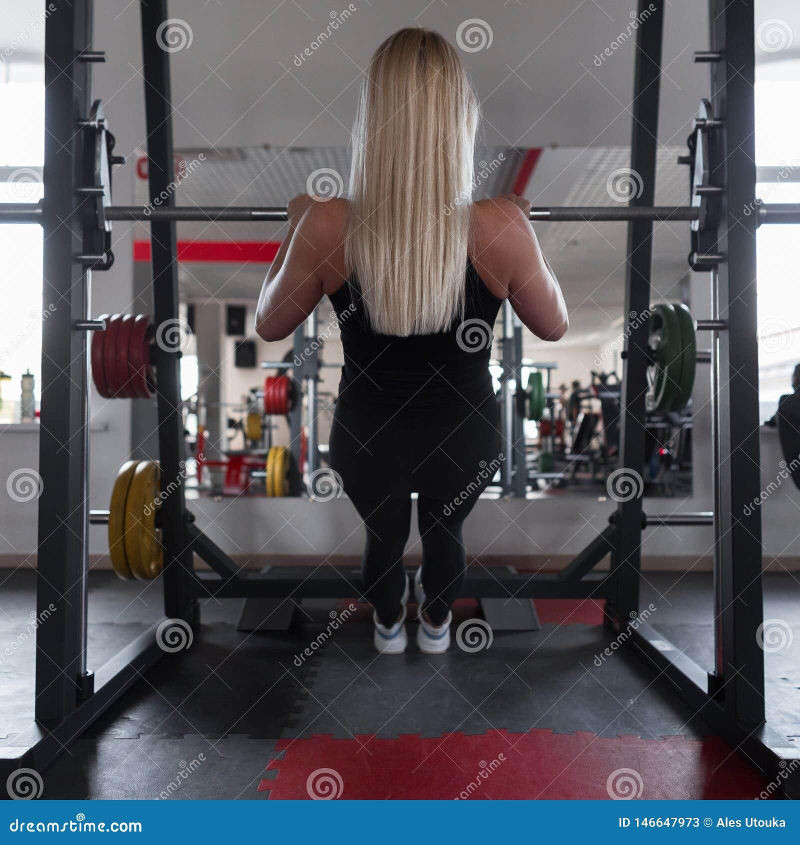 Sportowy trener młoda kobieta w czarnym sportswear w gym sneakers Dziewczyna robi ćwiczeniom w sprawności fizycznej studiu widok