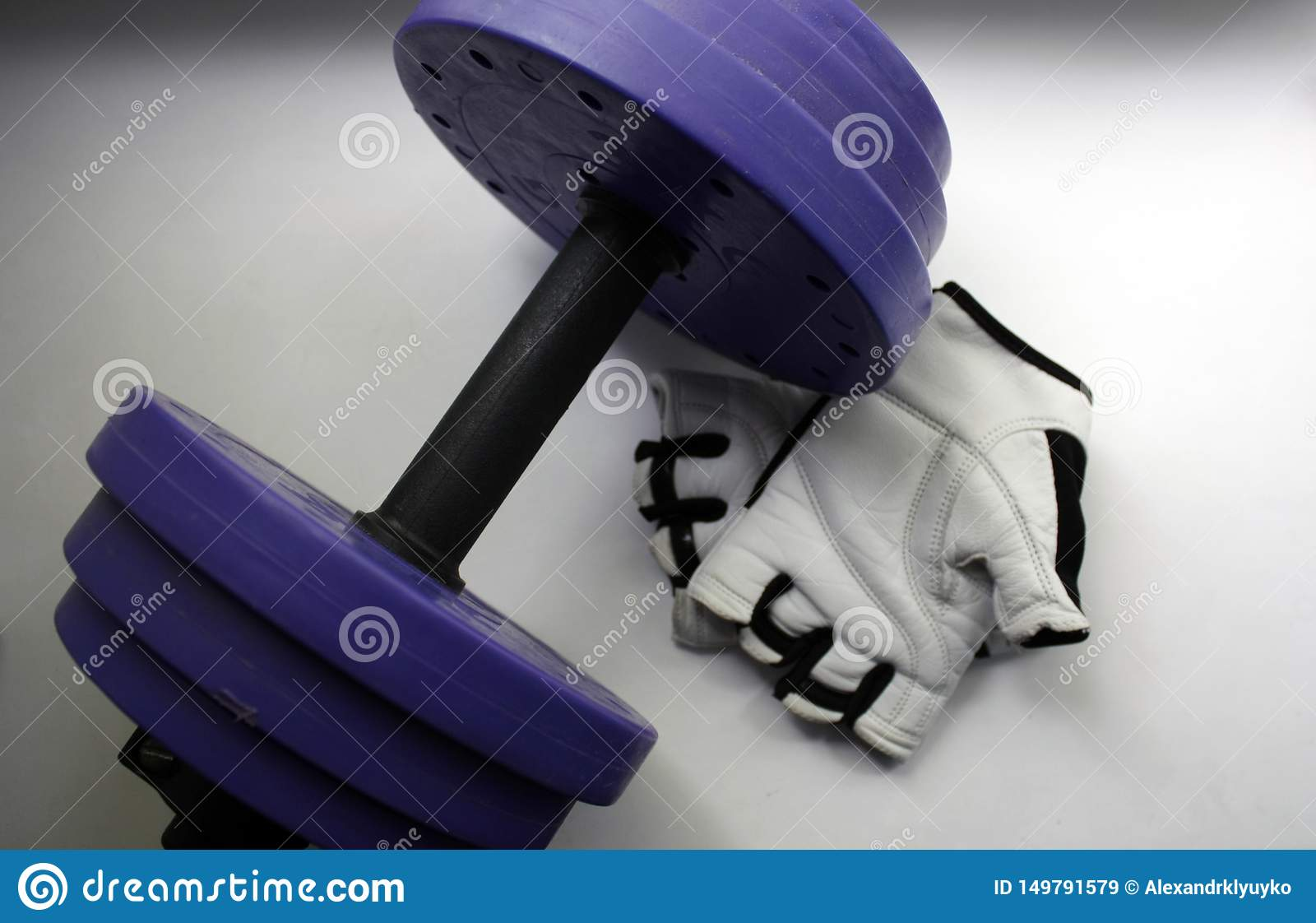 Sports accessories. Dumbbells, gloves, on a white background. Top view with copy space. Fitness, sport and healthy lifestyle