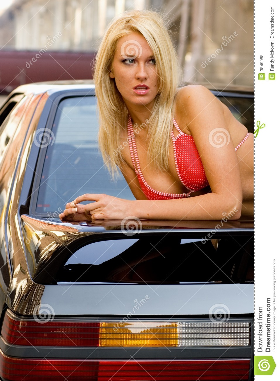 Sexy blonde fashion model in a swim suit laying on a black sports car