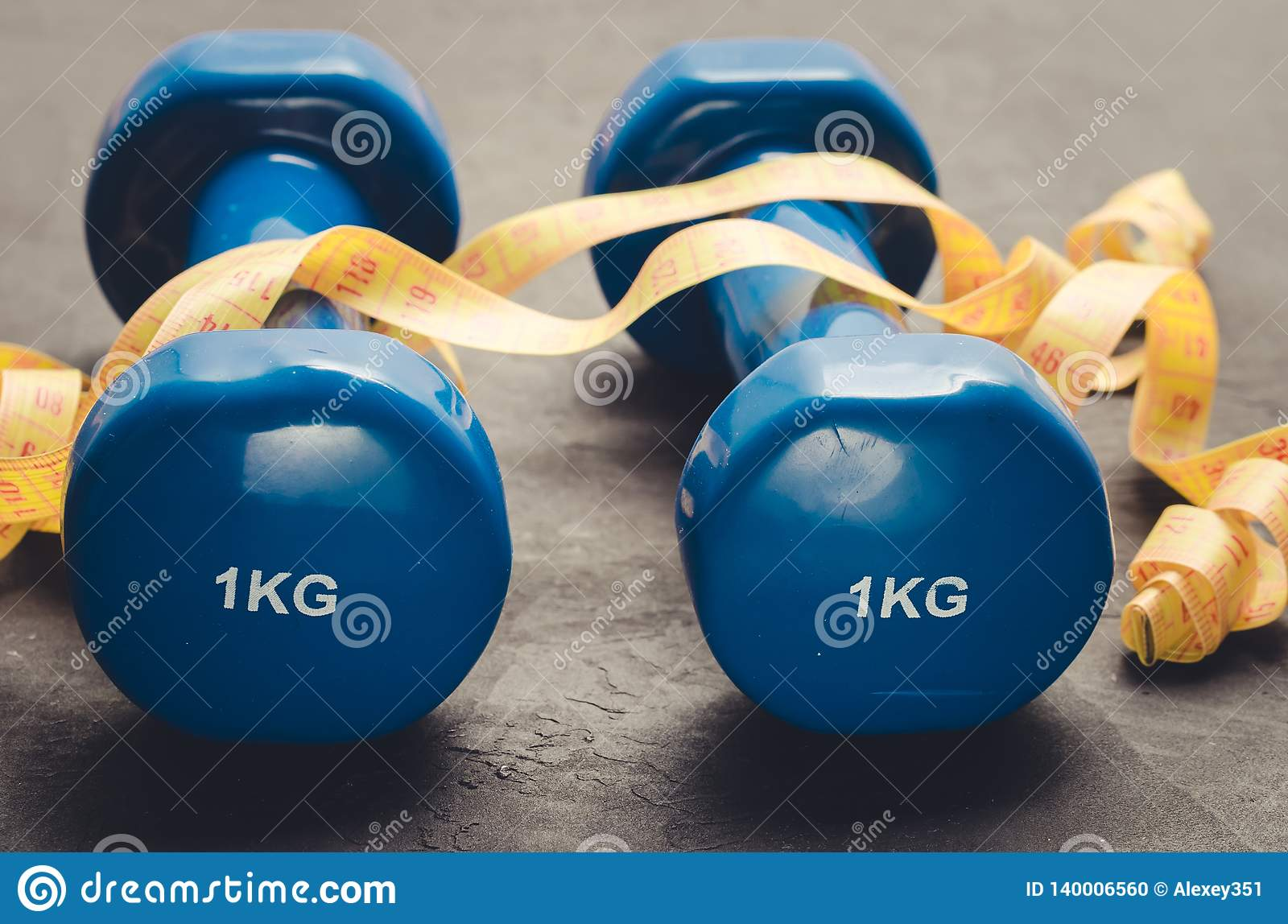 Sports equipment on a dark background/ Sports equipment with Blue dumbbells and yellow measuring tape. Selective focus