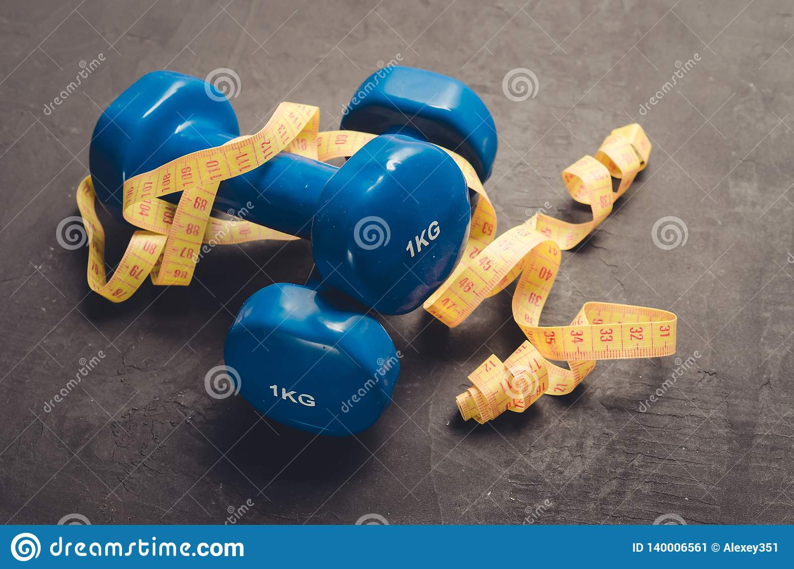 Sports equipment on a dark background. Top view/ Sports equipment with Blue dumbbells and yellow centimeter