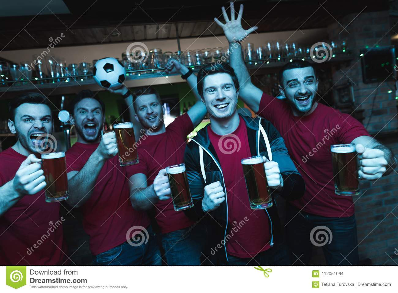 Sports fans celebrating and cheering in front of tv drinking beer at sports bar.