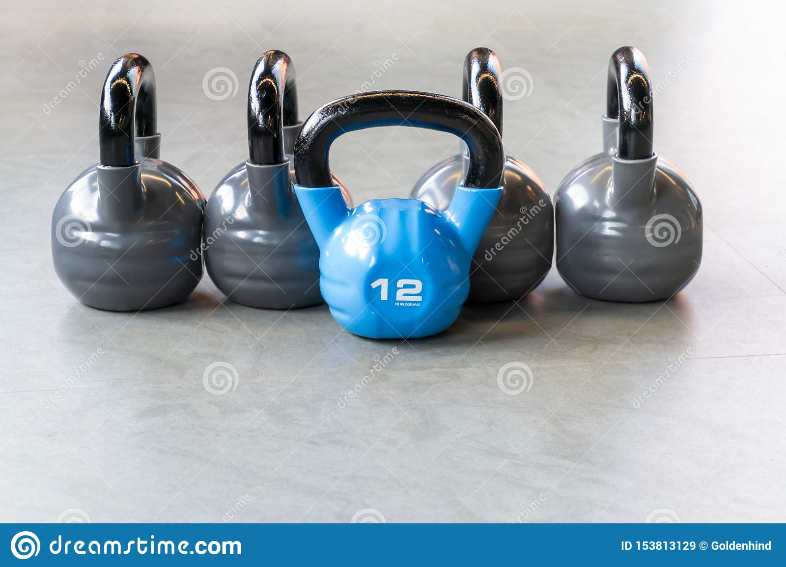 Sports, fitness or bodybuilding concept background. The composition of iron kettlebells on the floor in the gym