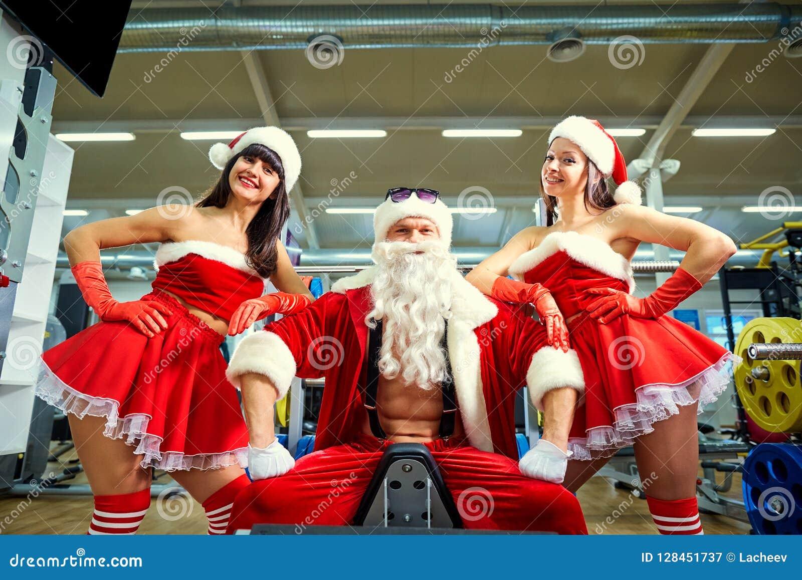 Sports Santa Claus avec des filles dans des costumes du ` s de Santa dans le gymnase