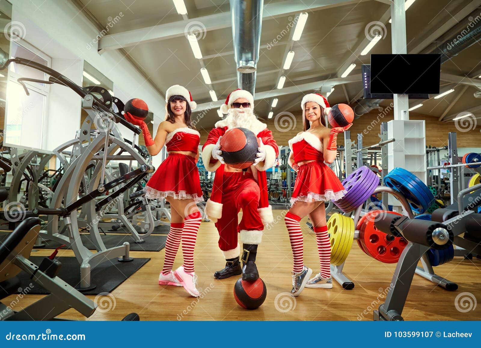 Sports Santa Claus avec des filles dans des costumes du ` s de Santa dans le gymnase dessus