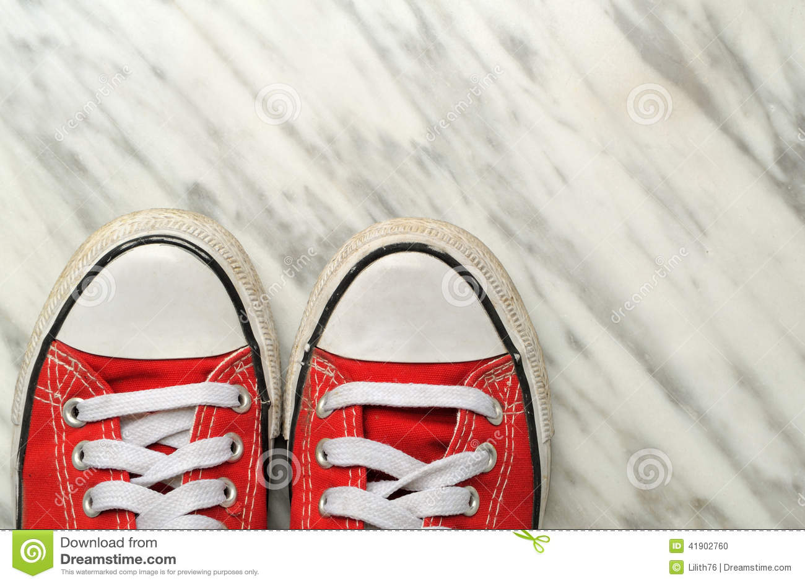 Sportshoes rojos usados en el fondo de mármol