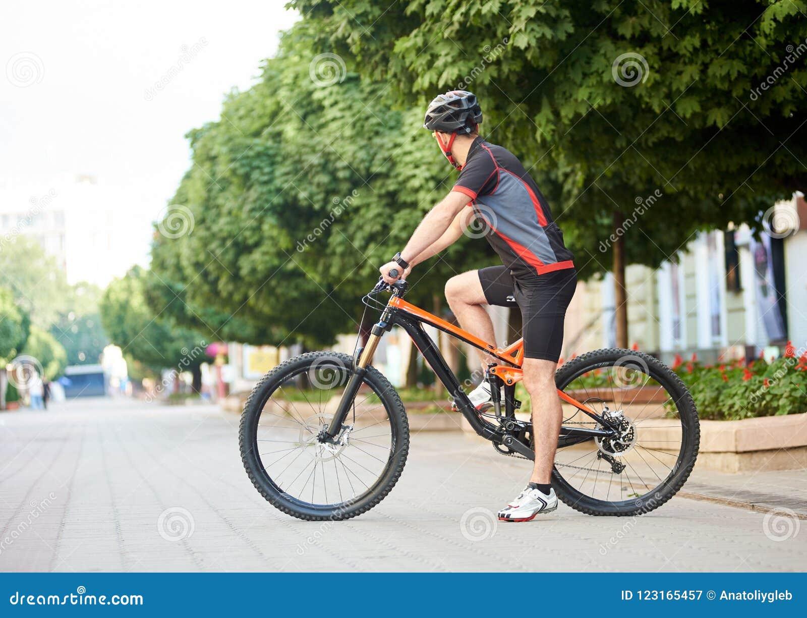 Sportsman crossing city street on bike