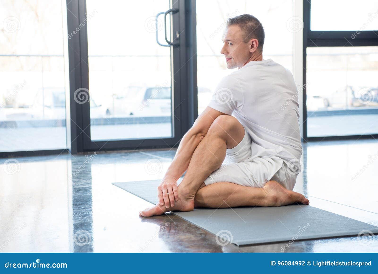 Sportsman in half spinal twist pose sitting on yoga mat