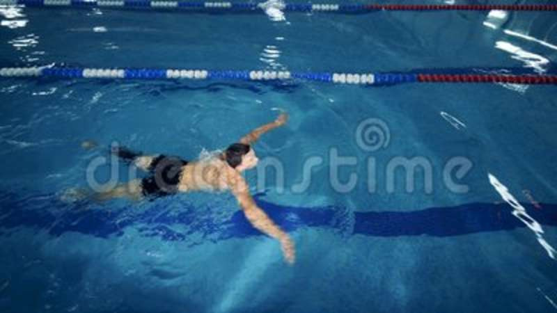 A sportsman with a leg prosthesis swims in a pool, top view. Man swims in a pool, wearing a prosthesis stock video
