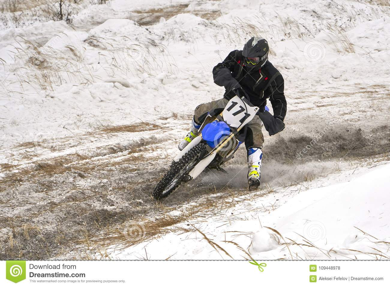 Sportsman racer man fulfills a fast ride on a motorcycle on the road extreme. The race track is very uneven.