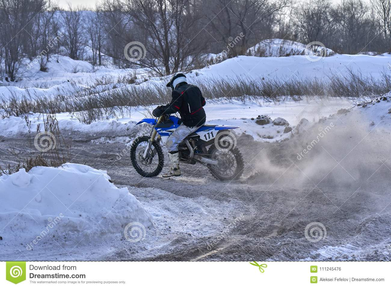 Sportsman racer man fulfills a fast ride on a motorcycle on the road extreme. The race track is very uneven. Photo as the racer p