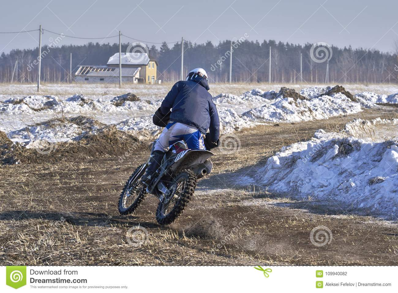 Sportsman racer man fulfills a fast ride on a motorcycle on the road extreme. The race track is very uneven