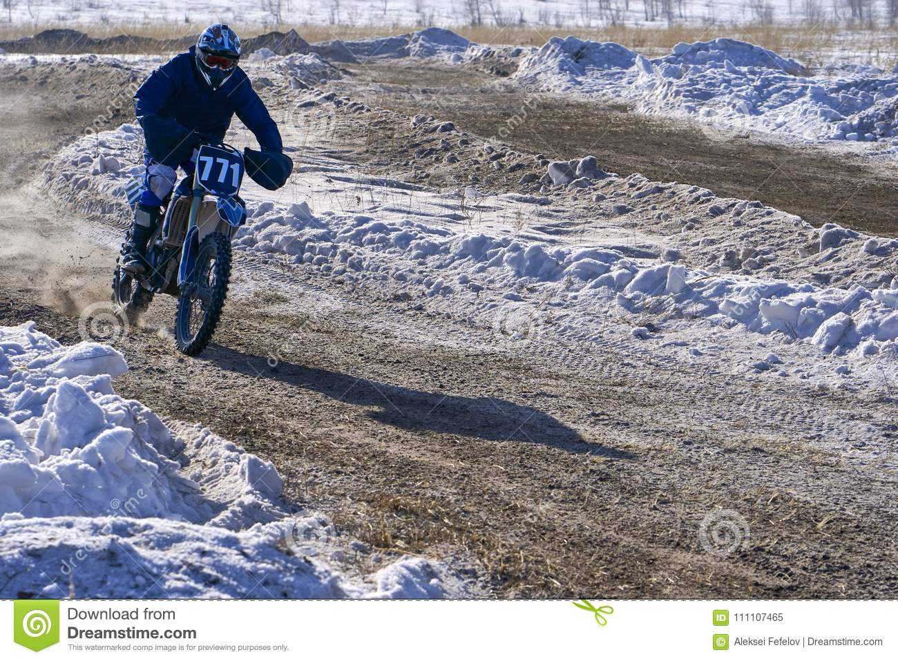 Sportsman racer man fulfills a fast ride on a motorcycle on the road extreme. The race track is very uneven. Sunny frosty winter d